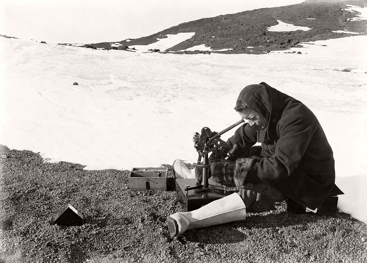 "Lieutenant Henry Rennick uses an instrument called an artificial horizon to take readings of Earth's natural horizon on February 9, 1911.  The Terra Nova scientific team was the largest to date in Antarctica, part of Scott's goal to ""take every advantage ... to study natural phenomena,"" as he wrote to the British Royal Geographical Society before his journey."