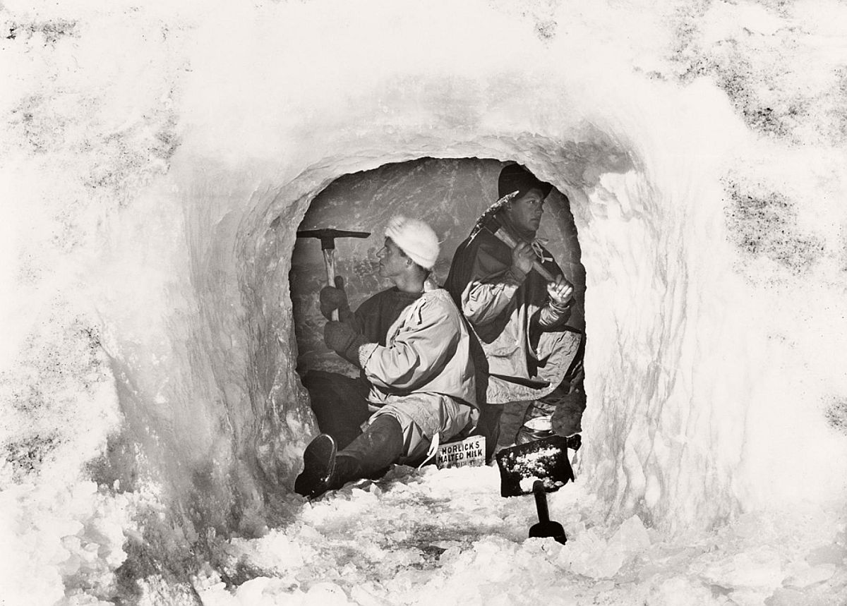 "Lieutenant Edward Evans and biologist Edward Nelson chisel an ice cave for food storage on January 12, 1911.  Though making it was ""slow and arduous work,"" Scott wrote in his journal, he predicted that, once complete, the larder ""will be admirable in every way."""