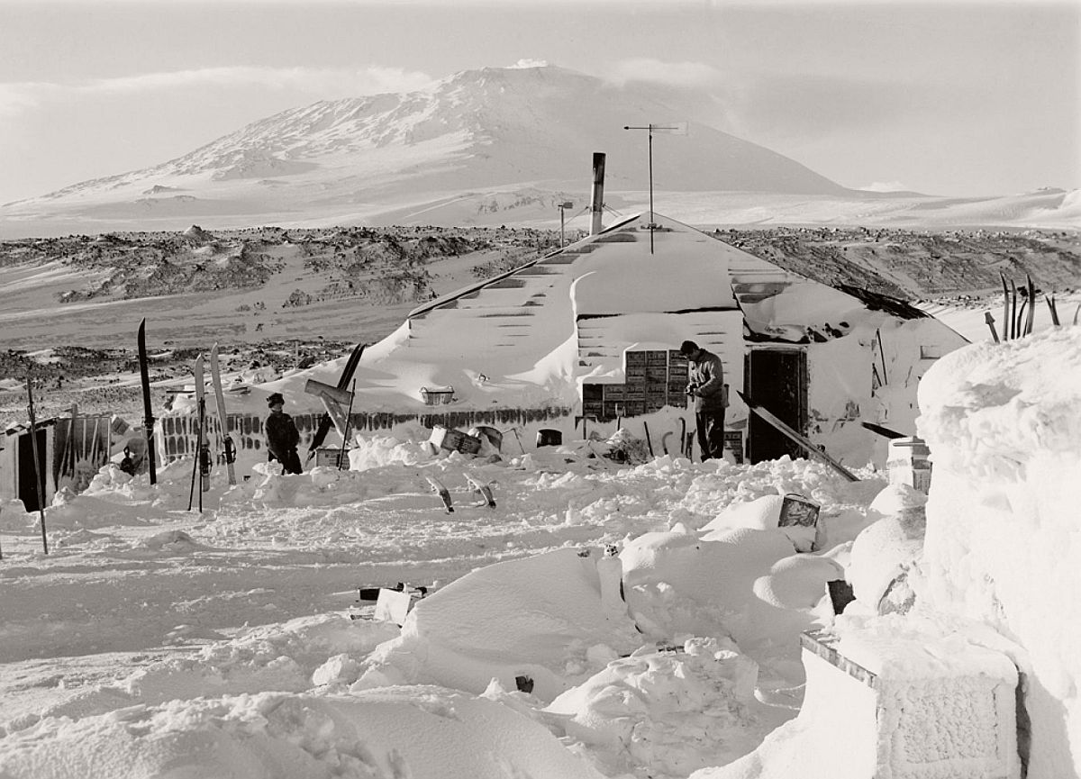 "Men emerge from the Terra Nova hut on September 17, 1911—a relatively ""warm"" spring day of -15 degrees Fahrenheit (-26 degrees Celsius).  The 12,447-foot-tall (3,794-meter-tall) Mount Erebus, Earth's southernmost active volcano, looms in the distance."