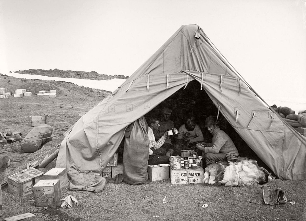Men eat lunch in a tent on January 7, 1911—not long after the Terra Nova landed at Cape Evans in Antarctica.  Scott chose to build the expedition hut at Cape Evans because the location provided easy access to the Ross Ice Shelf—a France-size piece of ice that would make up the first section of the South Pole trek.