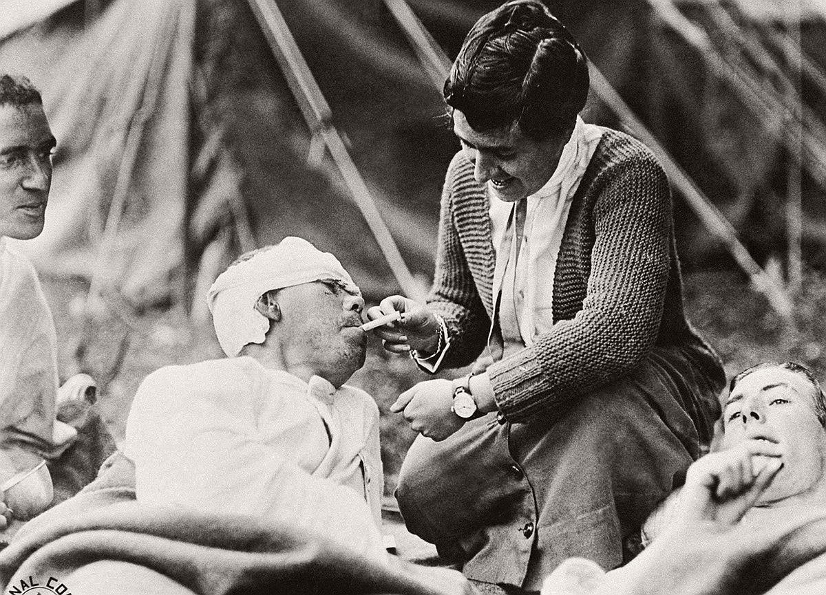 Private Ernest Stambash, Co. K, 165th Infantry, 42nd division, receives a cigarette from Miss Anna Rochester, American Red Cross volunteer at Evacuation Hospital No. 6 and 7, at Souilly, Meuse, France, on October 14, 1918. # AP