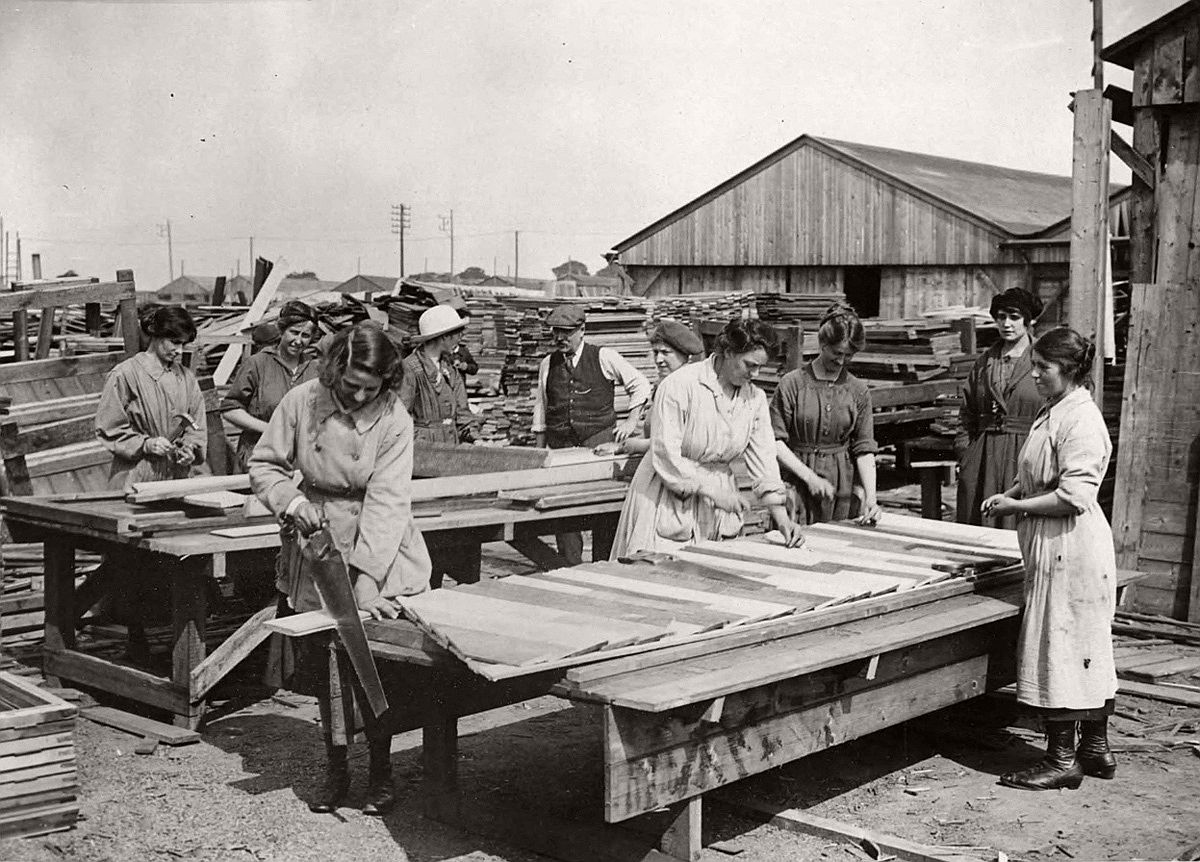 A group of female carpenters work in a lumber yard in France, constructing wooden huts. While they do not have a uniform, all the women appear to be wearing a protective coat or pinafore over their clothing. It is thought this photograph was taken by the British official photographer, John Warwick Brooke. Q.M.A.A.C. stands for Queen Mary's Army Auxiliary Corps. Formed in 1917 to replace the Women's Auxiliary Army Corp, by 1918 around 57,000 women made up the ranks of Q.M.A.A.C. # National Library of Scotland