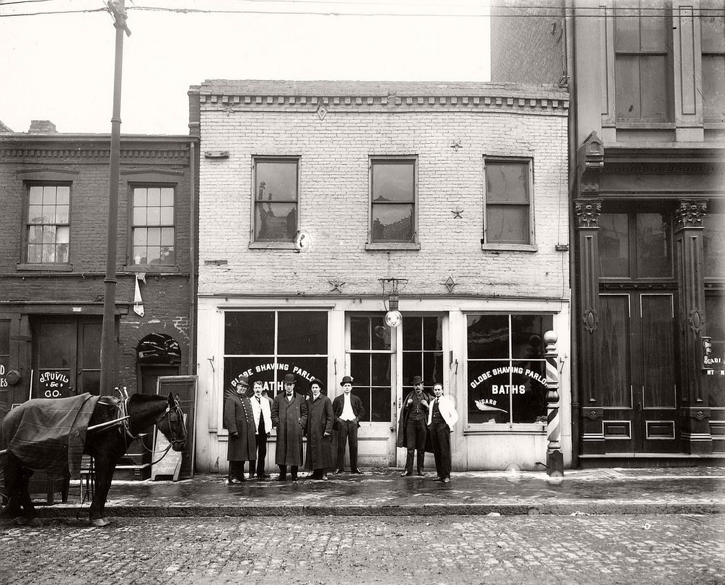 Group of men standing in front of the Globe Shaving Parlor at 1015 Carr Street, ca. 1910