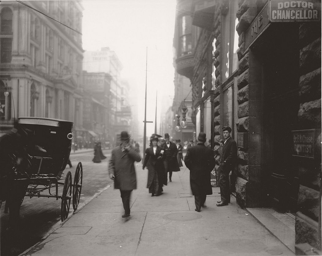 Pedestrians on the sidewalk near the intersection of Sixth and Locust Streets, ca. 1900s