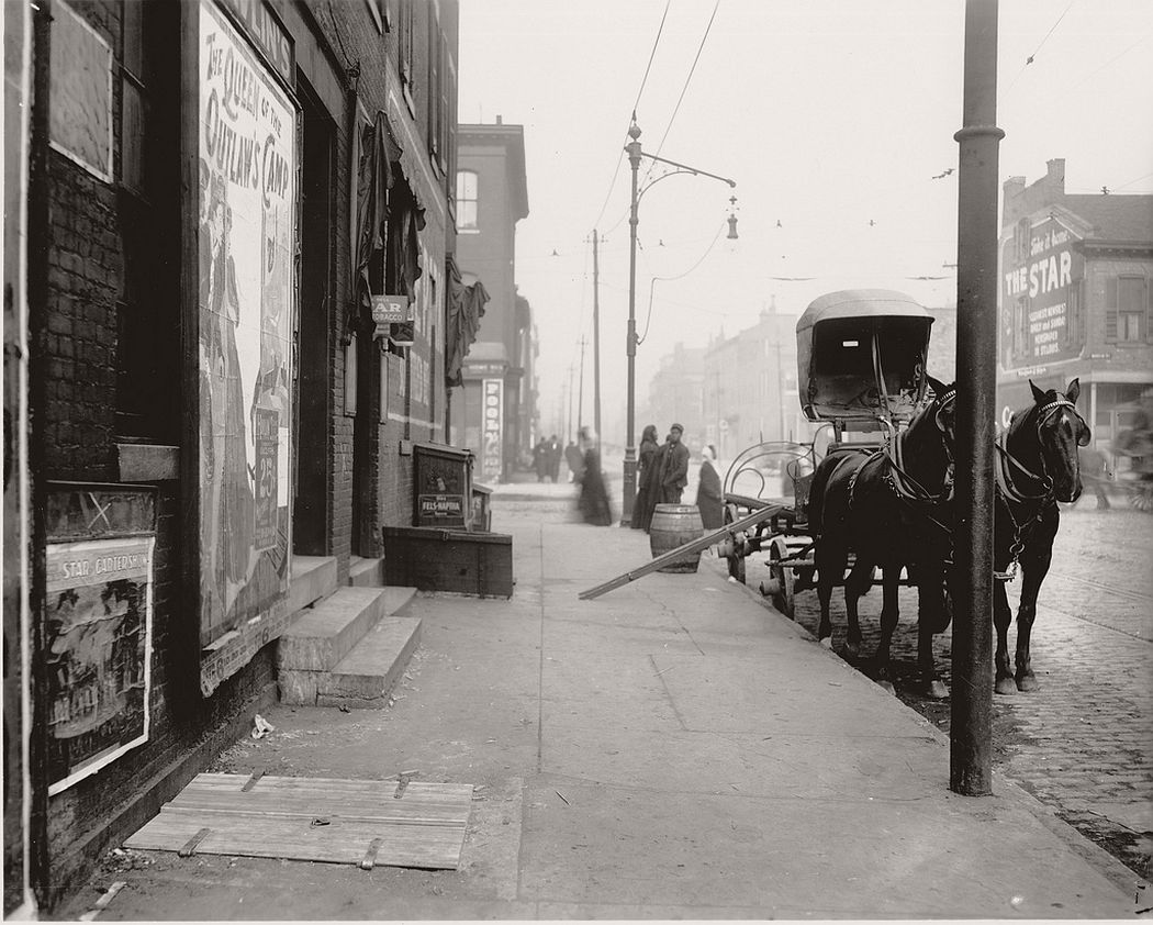 An empty cart for distributing beer in front of a bar on a street, ca. 1900s