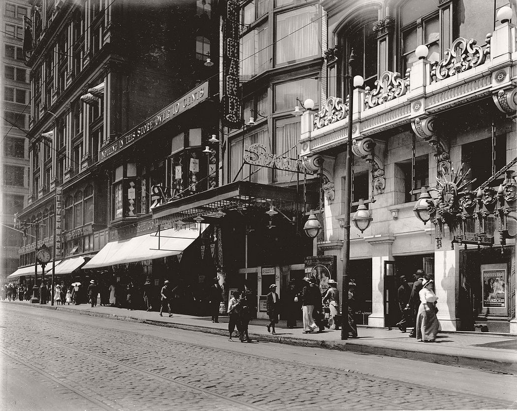 Pedestrians passing the F.W. Woolworth Company store at 413 N. Sixth Street and the Strand Theater box office, 1914
