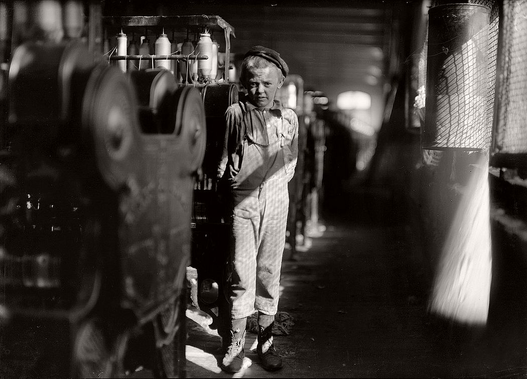 Boy stands next the machines that he has been working at for some months at the Avondale Mills, Birmingham, Alabama, November 1910