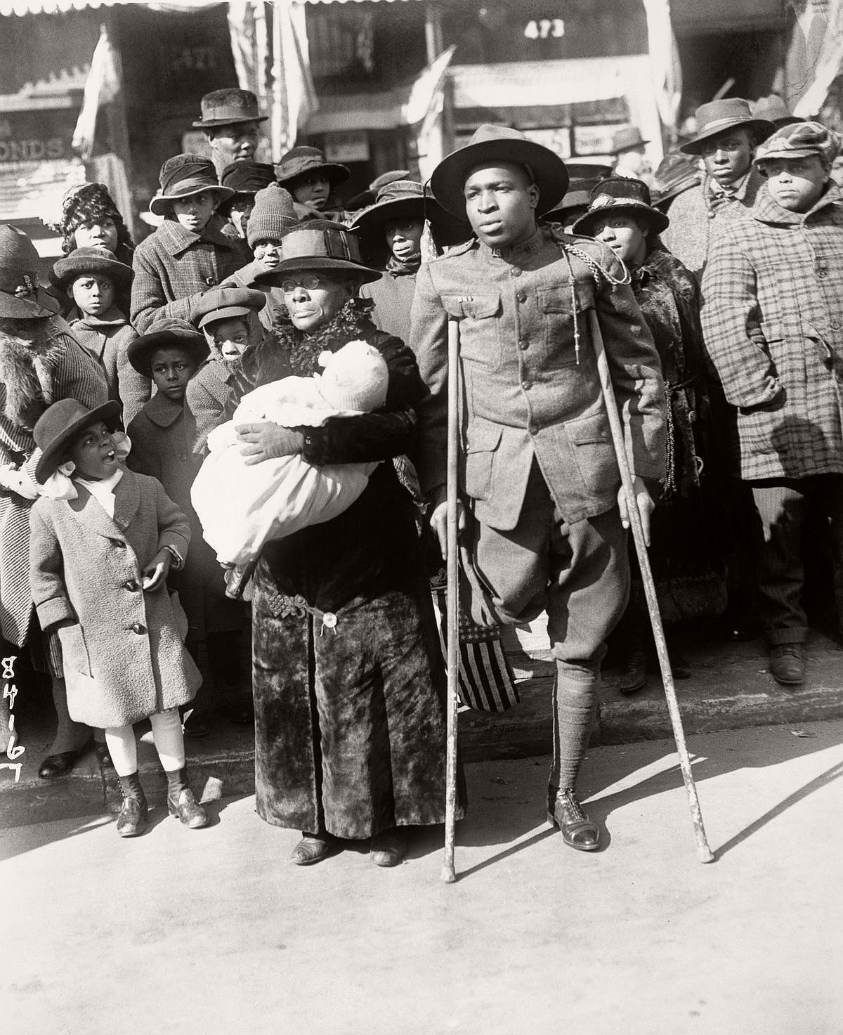 A wounded veteran watches the victory parade of the 369th. Feb. 17, 1919. (Bettmann/Corbis)