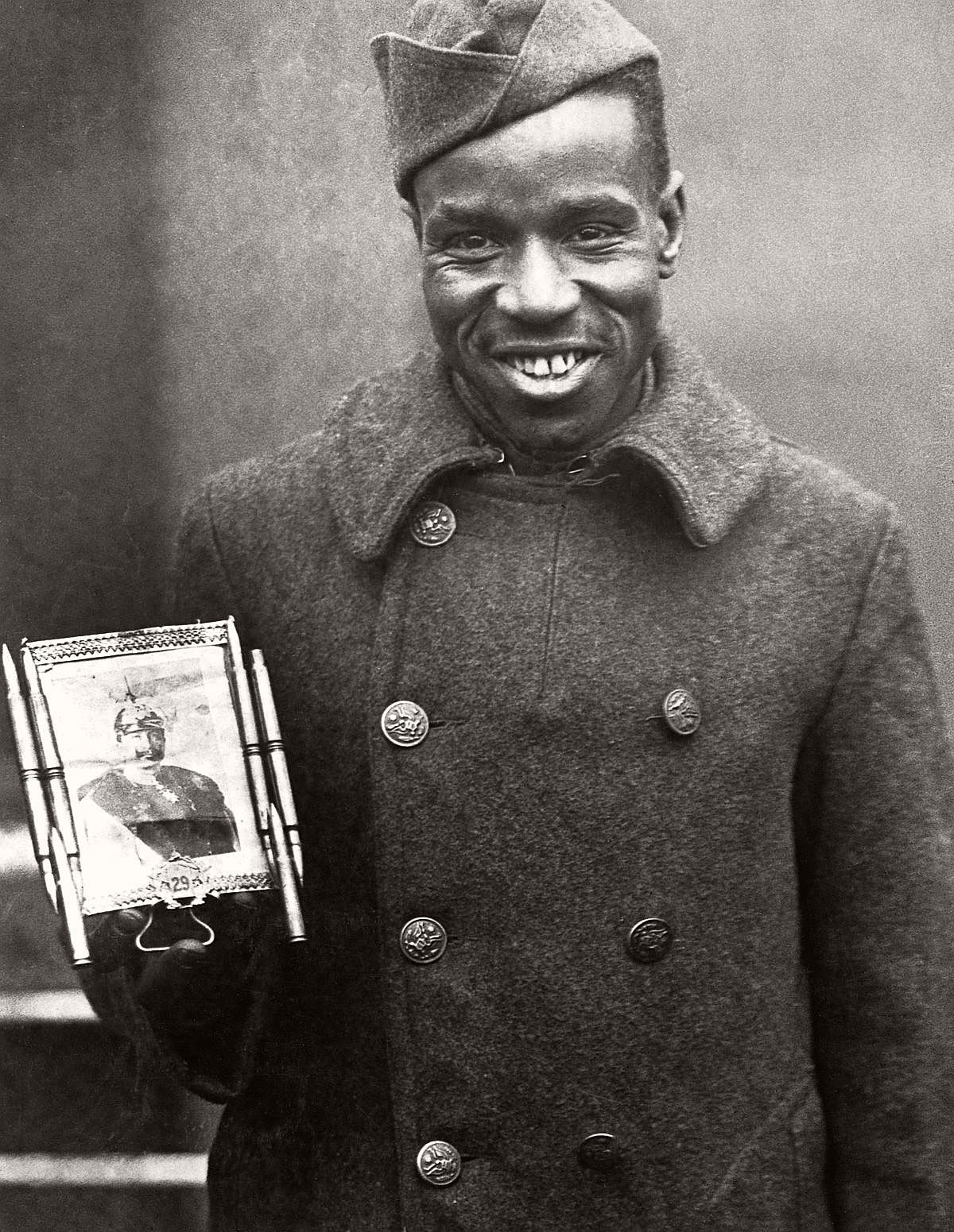 Cpl. Fred McIntyre of the 369th poses with a bullet-framed photo of Kaiser Wilhelm which he carries for good luck, c.1918. (Corbis)