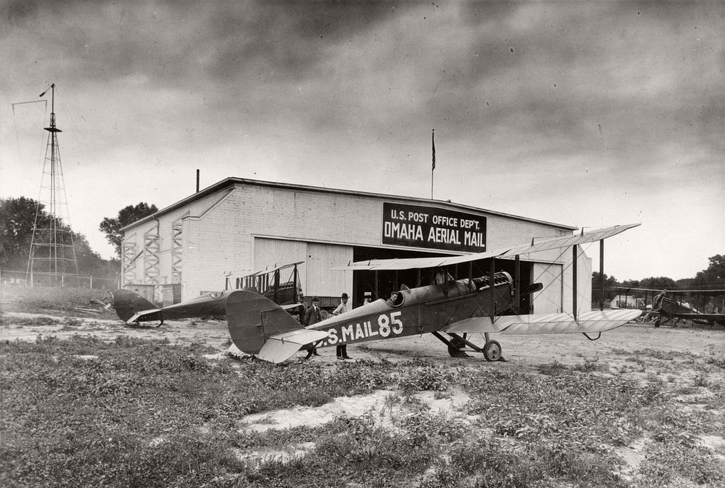 An airmail plane in front of a hangar on the Omaha, Nebraska airmail field, 1927