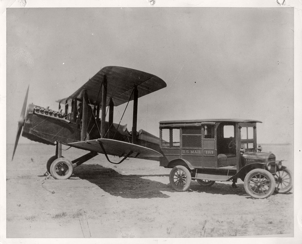 A de Havilland airmail plane parked on unidentified airfield next to a U.S. mail truck, 1922