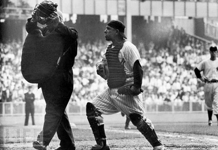 NY Yankee catcher Yogi Berra arguing with the home plate umpire who is walking away after giving the safe sign to Brooklyn Dodger Jackie Robinson's brilliant steal of home base in the 8th inning