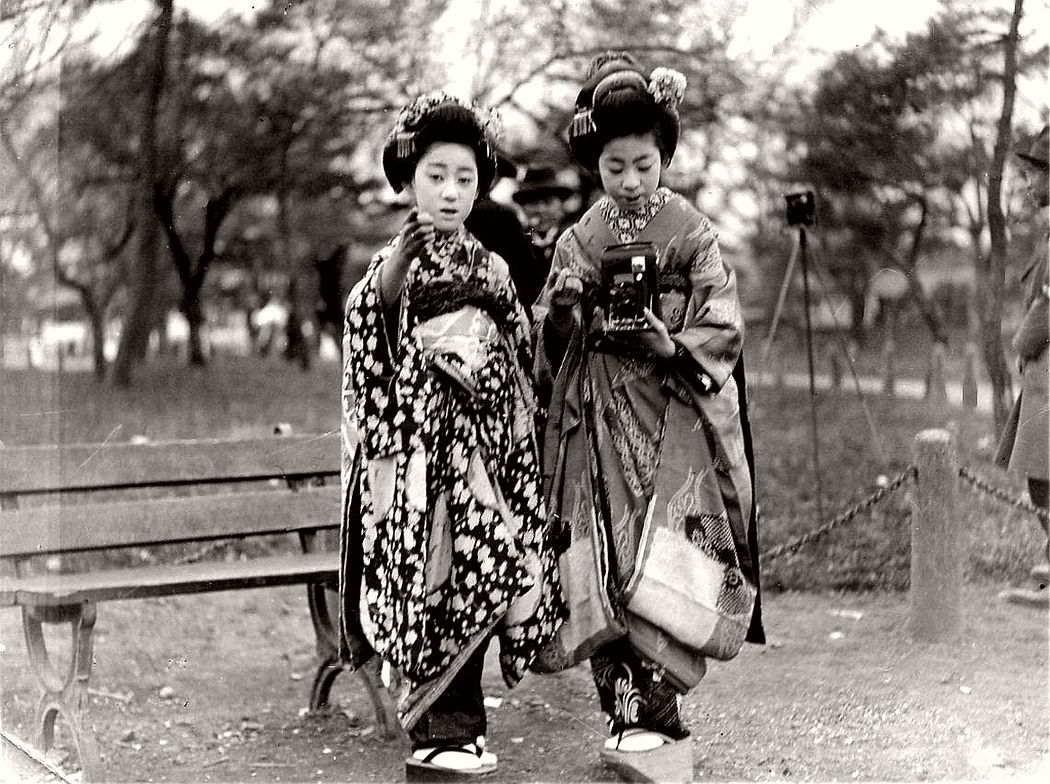 A Maiko girl taking a photograph with an early Kodak folding camera, while being guided by another Maiko, ca. 1920s