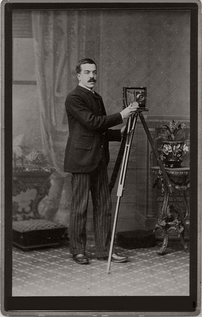 This cabinet card shows a mustached man with a folding camera in a studio setting.