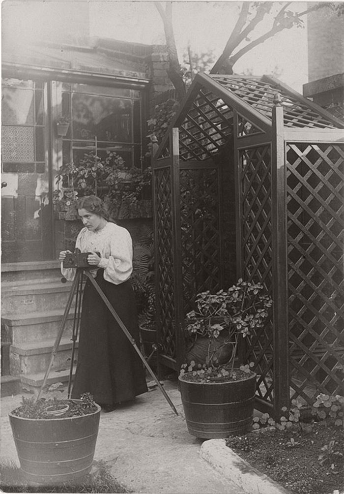 Young woman is standing behind a camera on a tripod in a back garden.