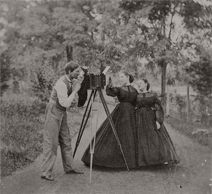 Two women in hoop skirts tease a photographer in this albumen print taken from an album of Mount Savage, Maryland photographs. The dresses suggest the 1850s/60s.