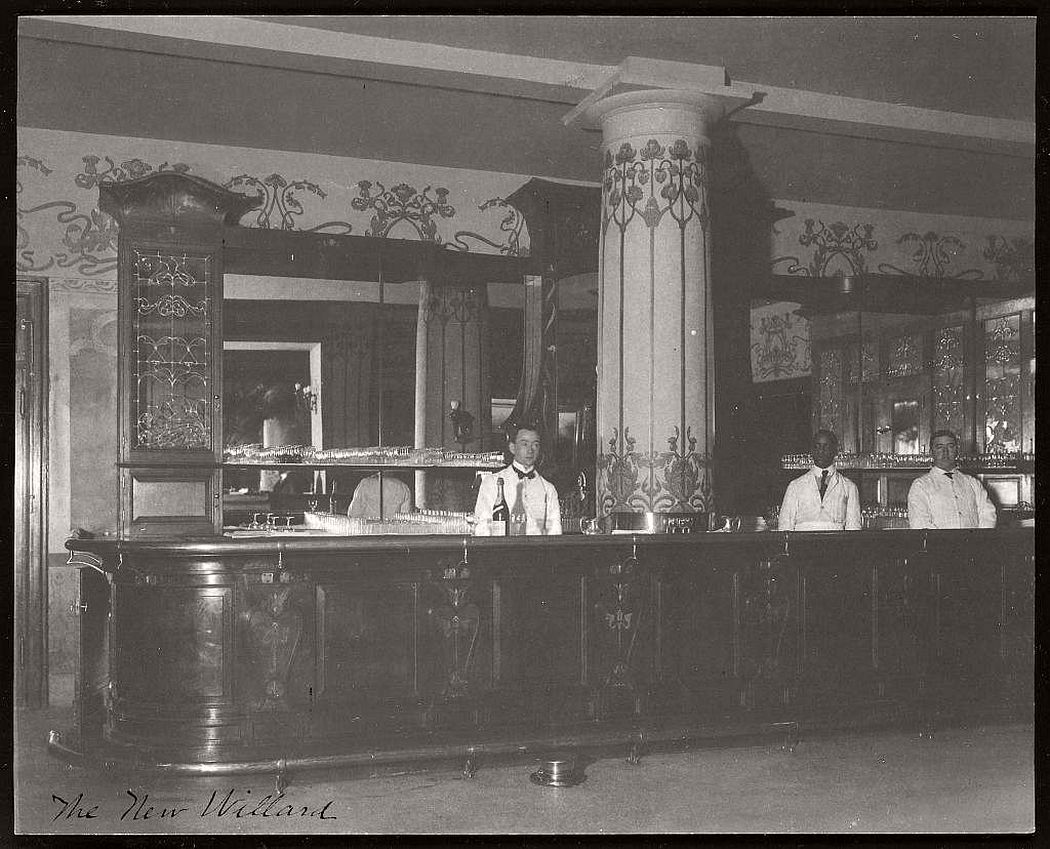 Three male employees, including one African American man, standing behind the bar at the Willard Hotel, between 1901 and 1910.