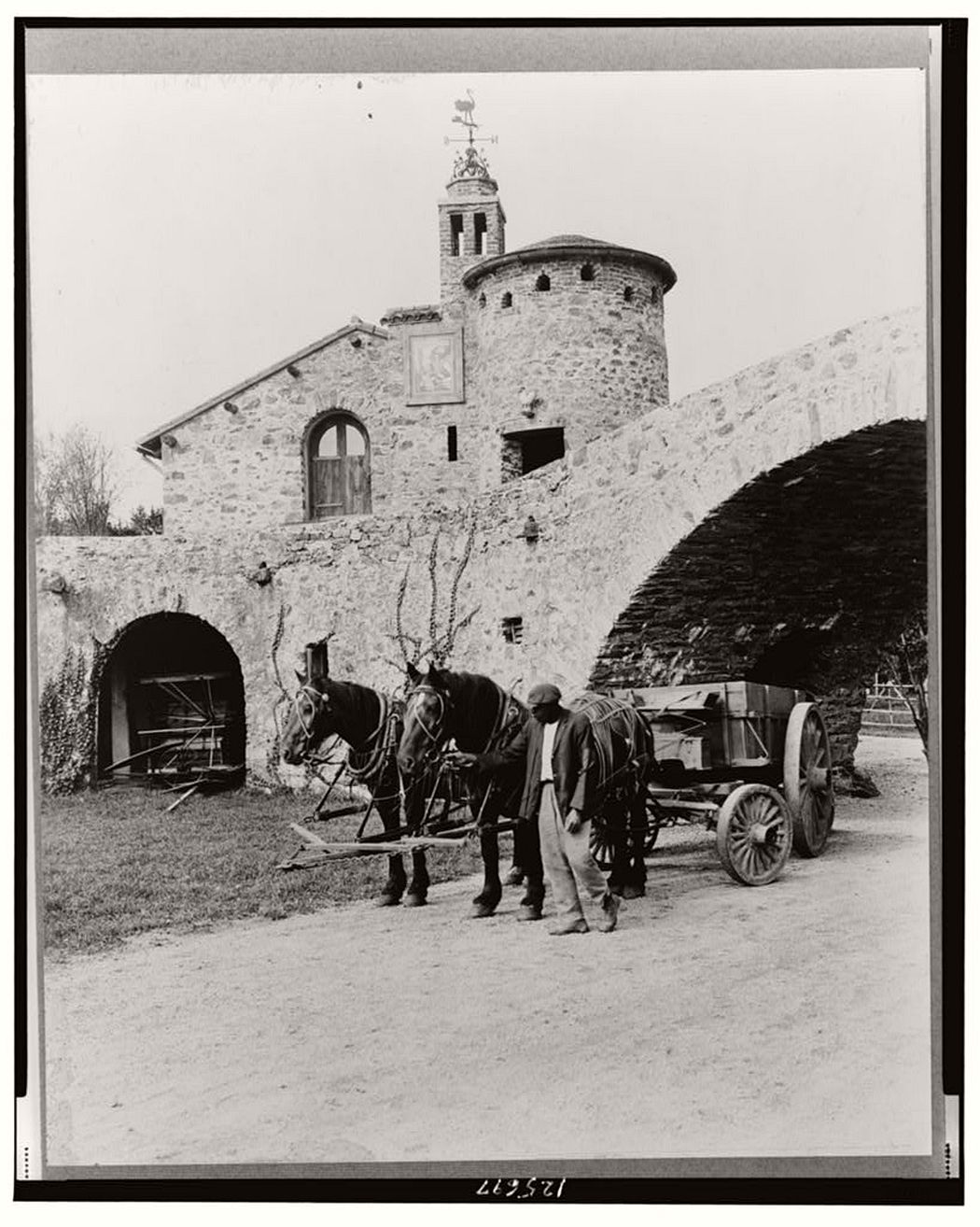 Courtyard with wagon and team and African American workman, 1917.