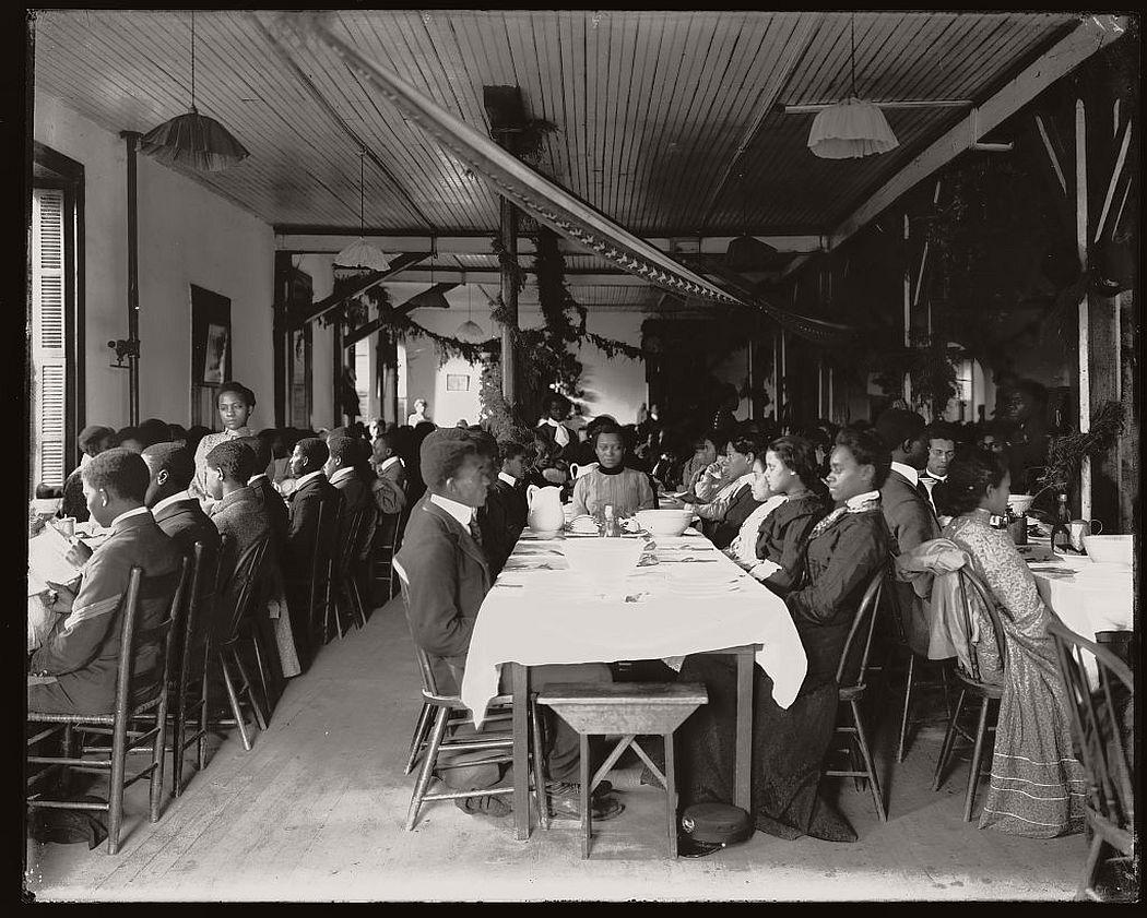 Interior view of dining hall, decorated for the holidays, with students sitting at tables at the Tuskegee Institute, ca. 1902.