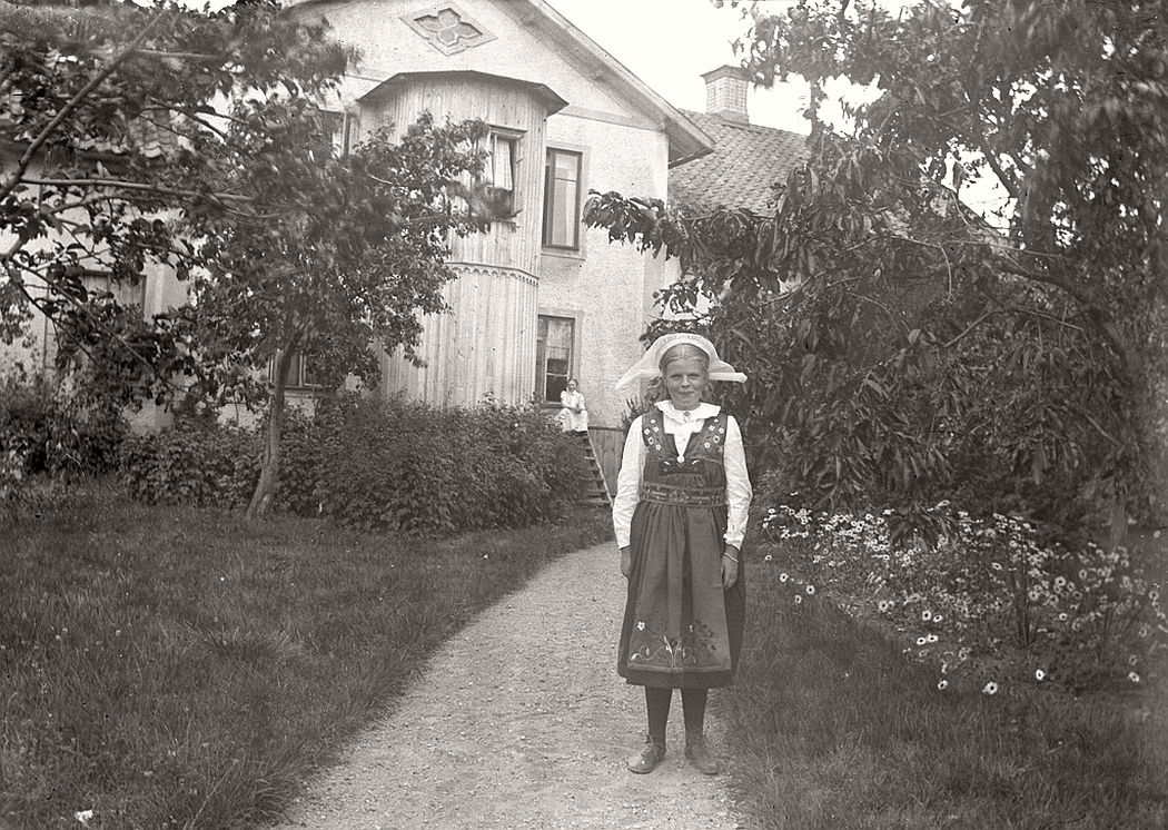 The girl in the beautiful Sweden suit is not certain identified yet. But the photo was taken outside the State Building in Hästeryd, Frinnaryd 1915.