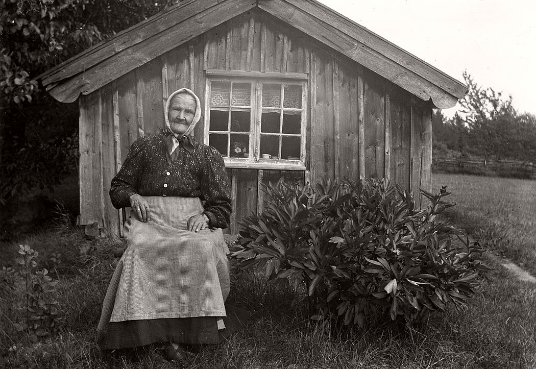 Grandmother sitting in front of her cottage.