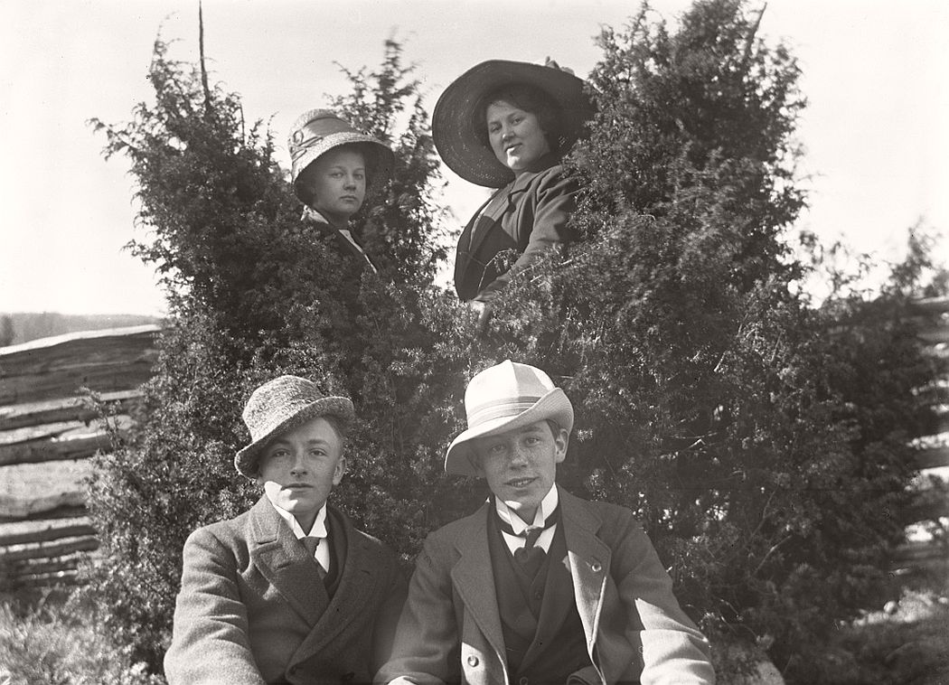 Two in front and two behind the junipers. The women in the background is Carola Aurell and Maria Andersson. The young man on the left is called Henning Aurell and is the brother of Carol Aurell. The man on the right is not yet identified.