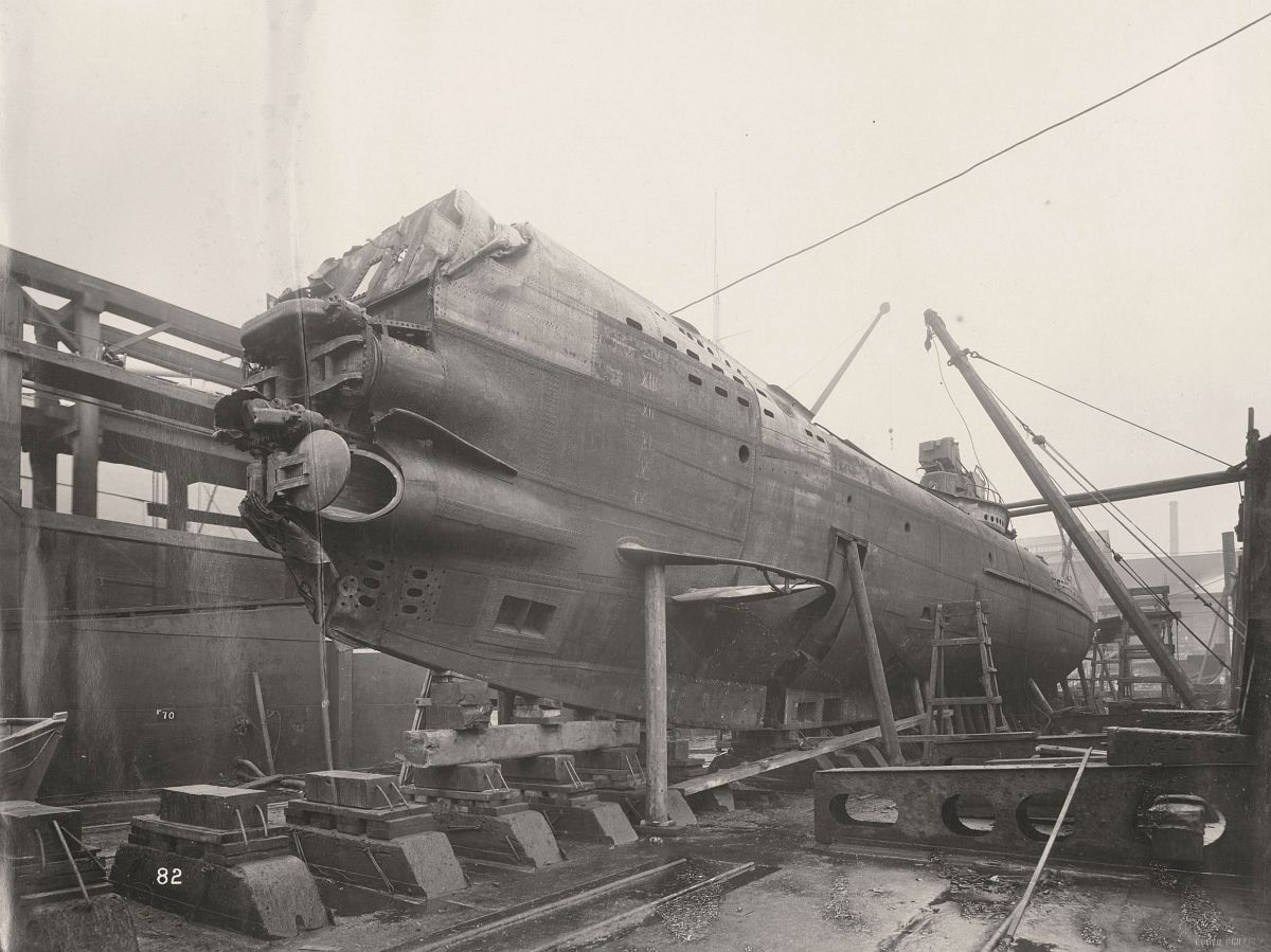 This photograph shows the U-Boat 110, a German submarine that was sunk and risen in 1918. This photograph shows the Submarine's Four bow Torpedo Tubes & hydroplane on the port side.