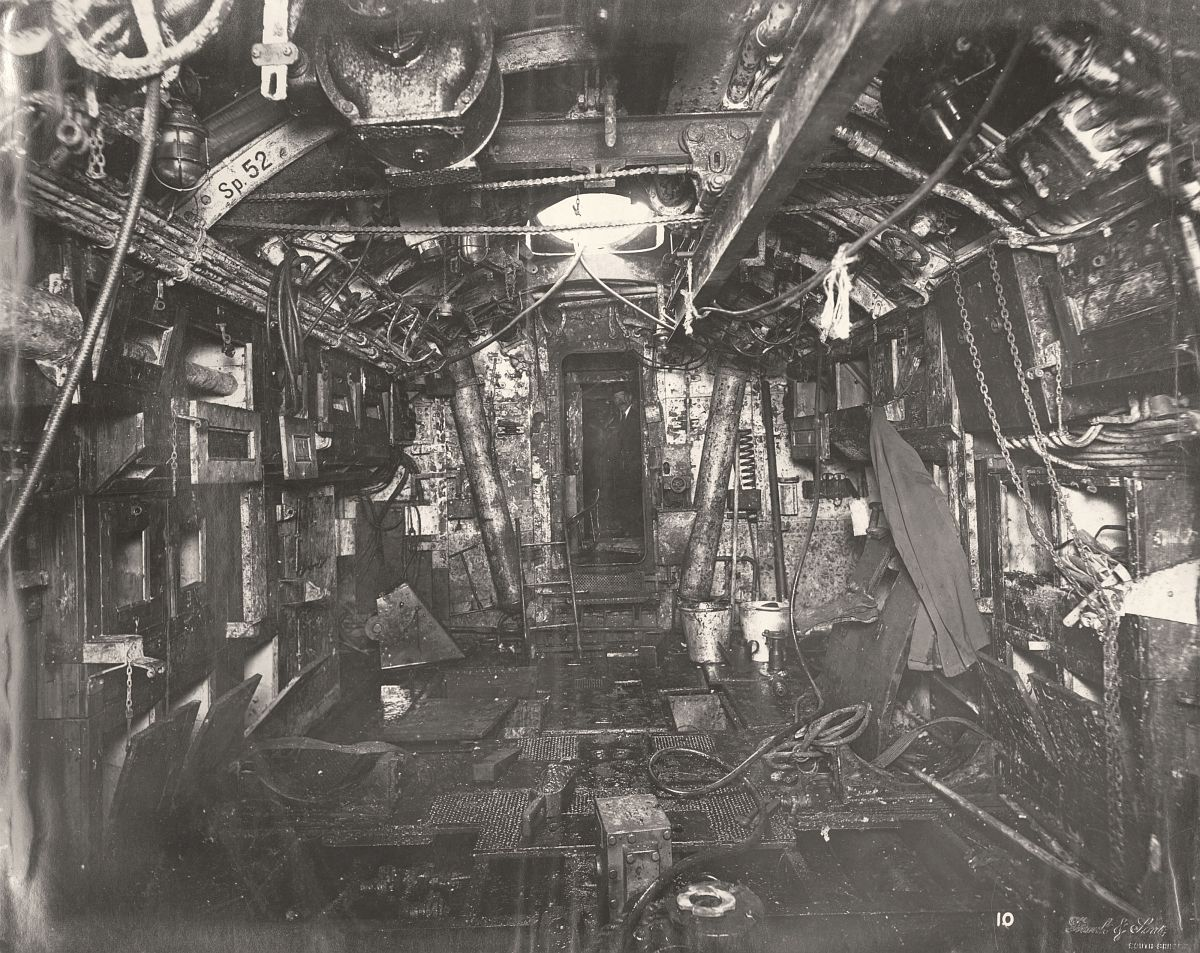 This photograph shows the U-Boat 110, a German Submarine that was sunk and risen in 1918. This photograph shows the Submarine's Torpedo Room looking aft, including a Torpedo lifting beam overhead.