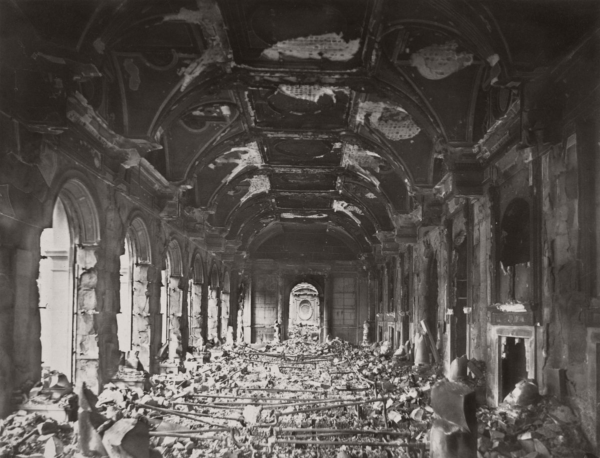 Photograph shows the charred remains of the once lavish audience hall of the Council of State in the Palais d'Orsay, a building begun by Napoleon I, completed in 1840 under King Louis-Philippe, and burned by the Communards on May 23, 1871. In the last years of the nineteenth century, these ruins were replaced by a new railway station, the Gare d'Orsay.