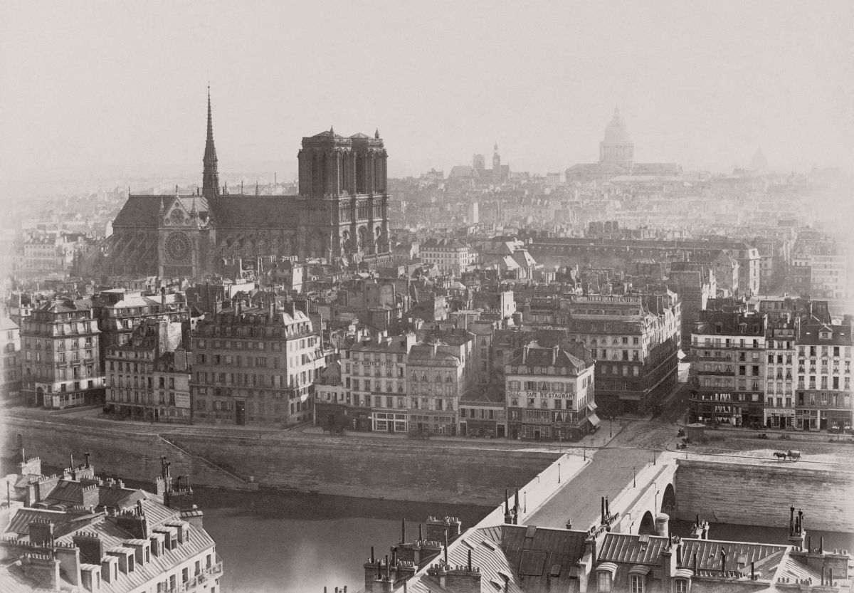 Photograph shows view of Notre-Dame de Paris rising above Ile de la Cité. 1865.