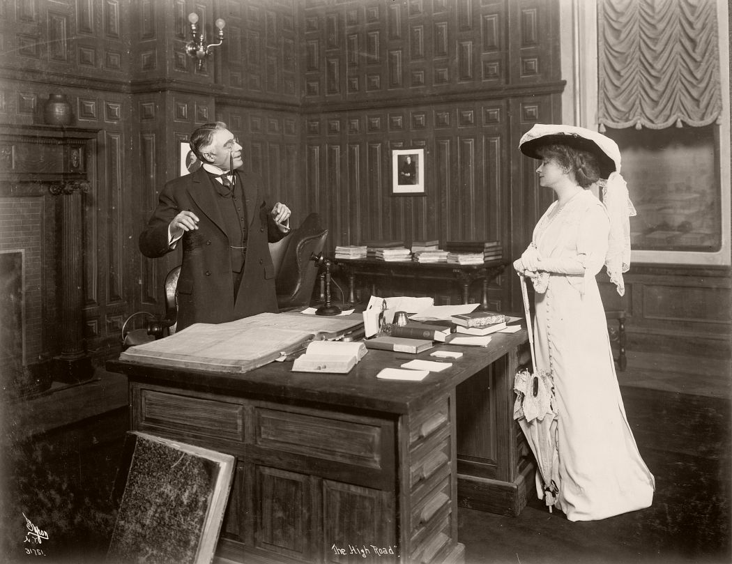 "A scene from the play ""The High Road"" by American playwright Edward Sheldon (1886-1946), in which a male character, played by Frederick Perry, speaks across a desk to a female character, played by Minnie Maddern Fiske. Photographed by Joseph Byron, 1912"