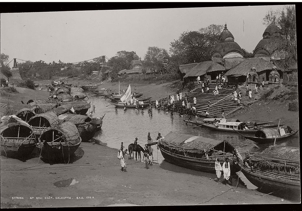 A group of people bathing at Kalighat near boats on river and ashore. Suspension bridge in the distance.