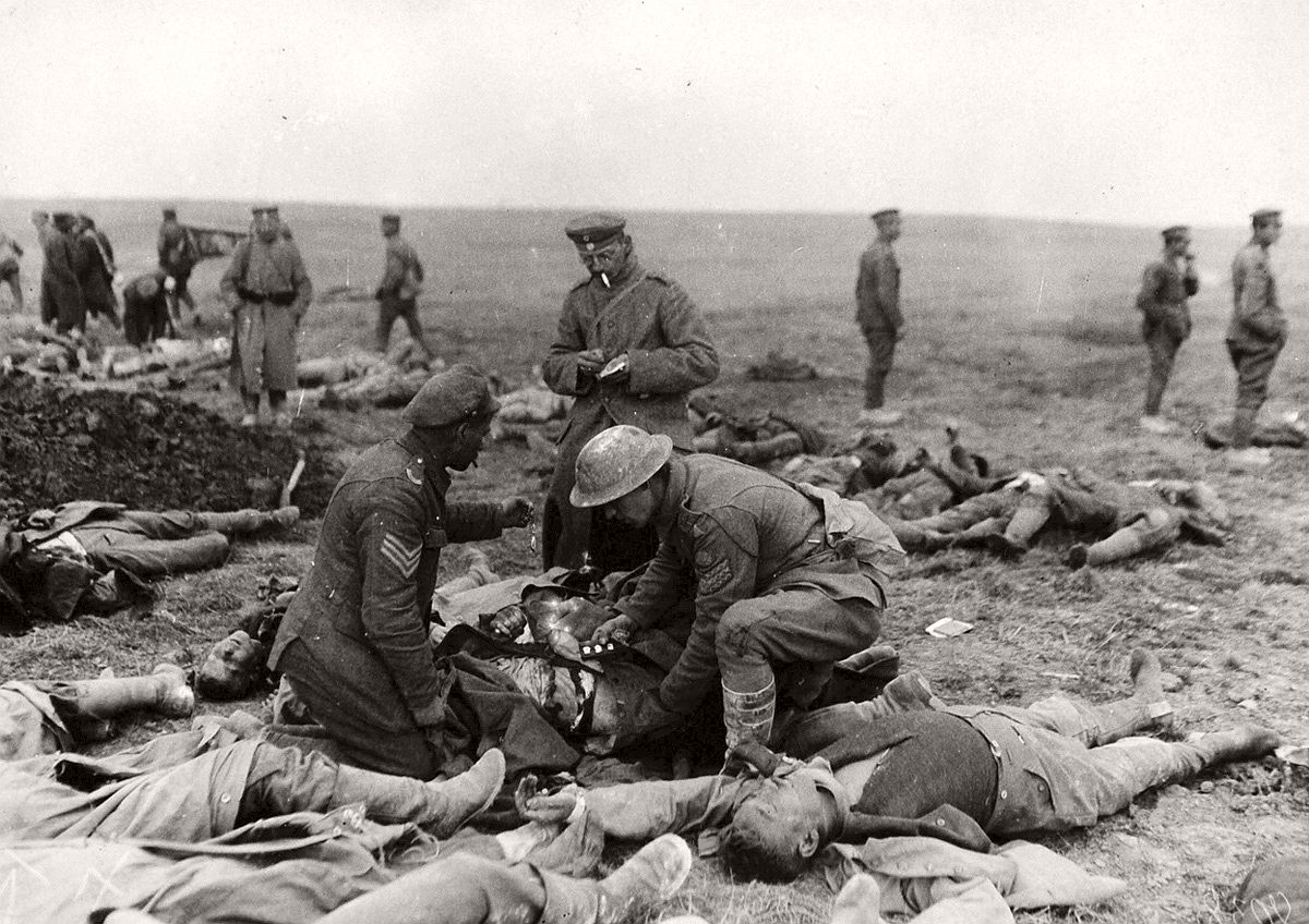 Western Front. A Captured British soldier salvages the valuables of fellow Englishmen killed in battle, in April of 1918. # National Archive / Official German Photograph of WWI