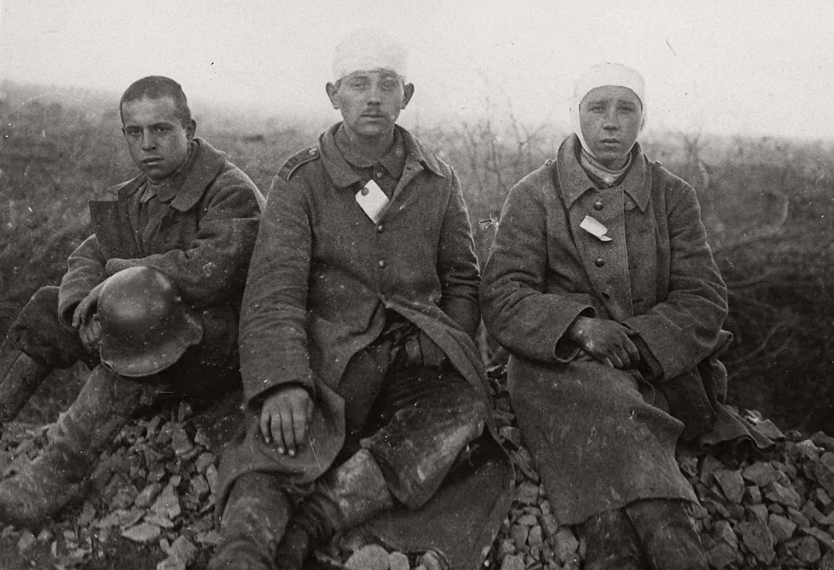 Three young-looking German prisoners of war. Their clothes are caked in mud and are a mishmash of styles. The soldier on the left still has his helmet, but the others have bandages wrapped round their heads. # National Library of Scotland