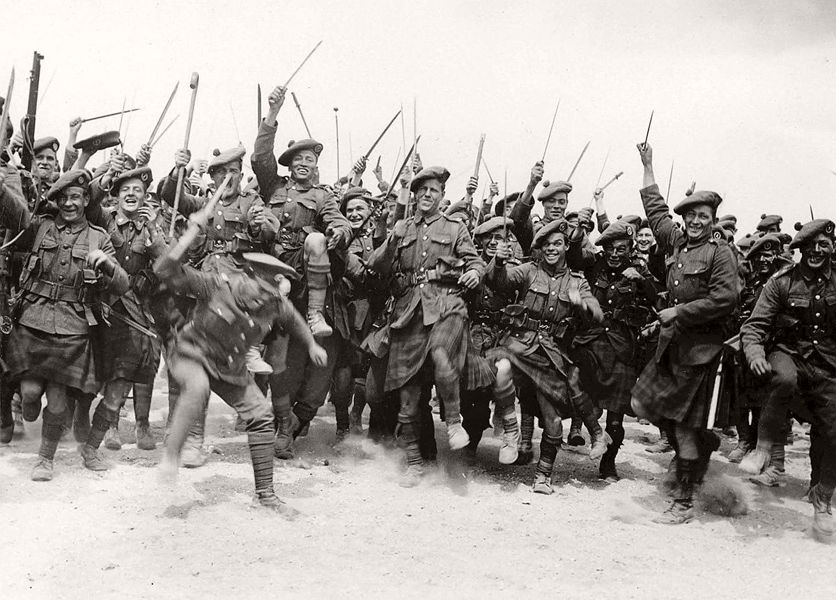 A large group of soldiers, likely South African infantry, having a good time. They are stamping their feet and brandishing anything that comes to hand, from walking sticks to swords. It is all being done in a light-hearted fashion, with most of the men pulling funny faces and smiling. Many of the soldiers are wearing kilts and balmorals. # National Library of Scotland