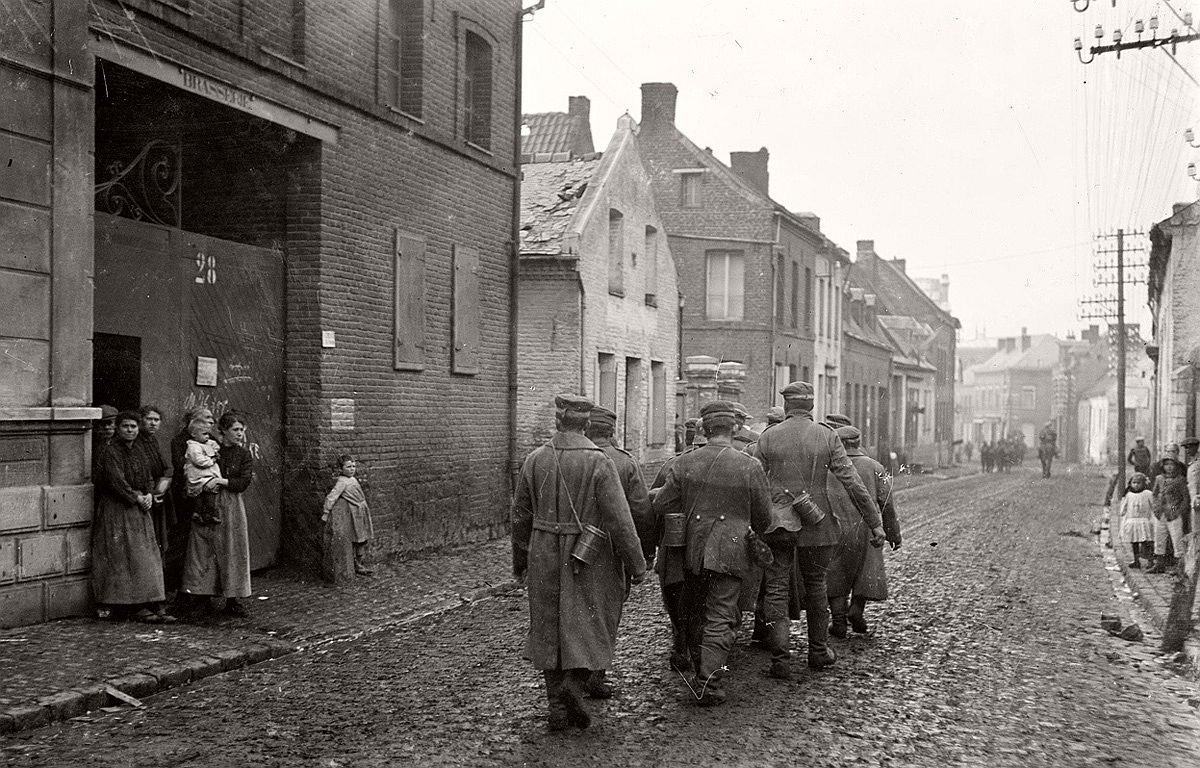 Watched by a group of locals, German prisoners of war walk down a street in the French town of Solesmes, on November 1, 1918, near the end of World War I. # Henry Armytage Sanders / National Library of New Zealand