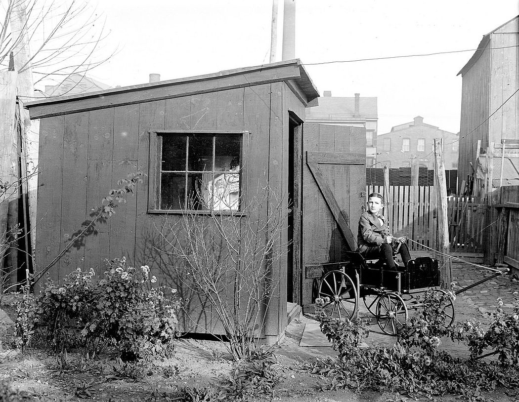 Boy with toy wagon in front of his house in Trenton