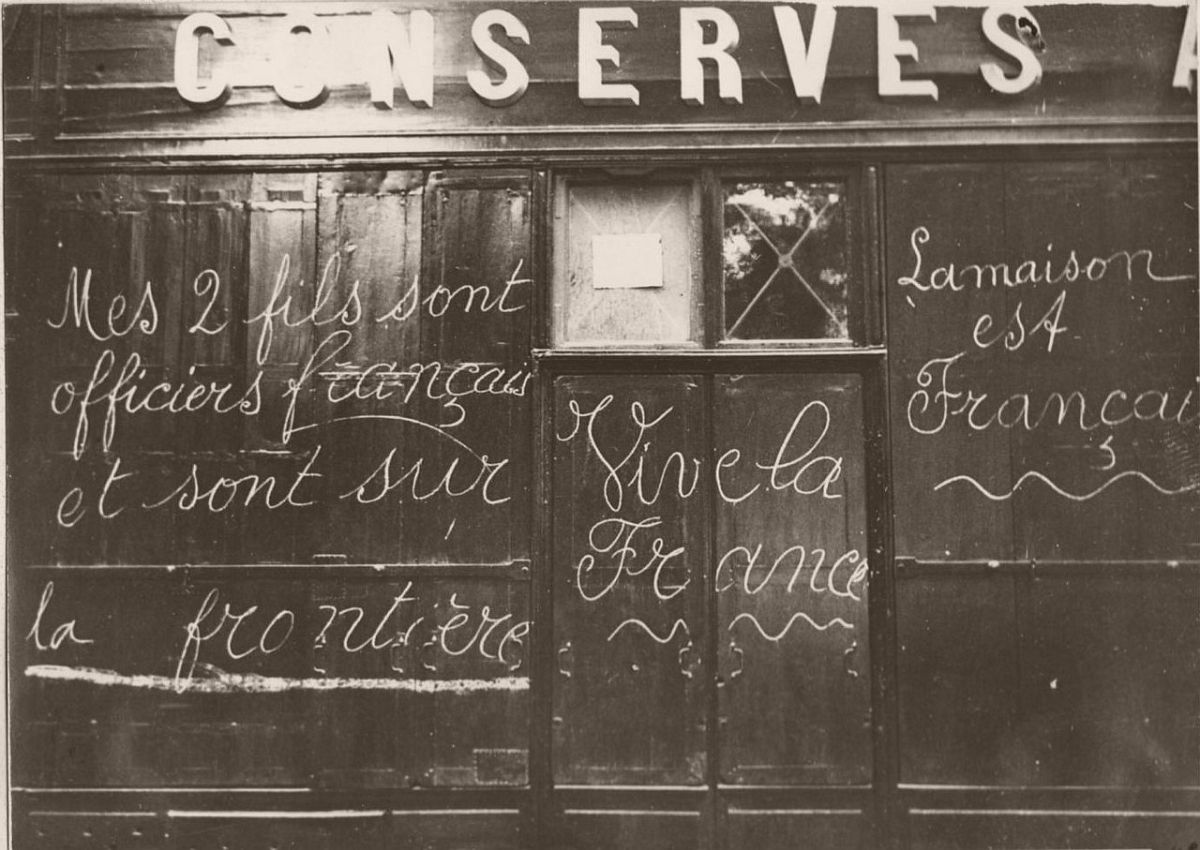 1914. Sign explaining that the owner of this shop has his two sons mobilized.
