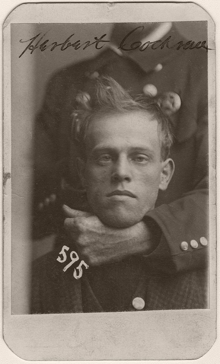 An unidentified member of the Omaha police force holds Herbert Cockran in a headlock during his mug shot. Cockran was arrested on November 24, 1899, for burglary. A tailor from Fairmont, Nebraska, Cockran had a slightly stooped build with a fair complexion and his eyebrows met at the root of his nose, according to the police description.