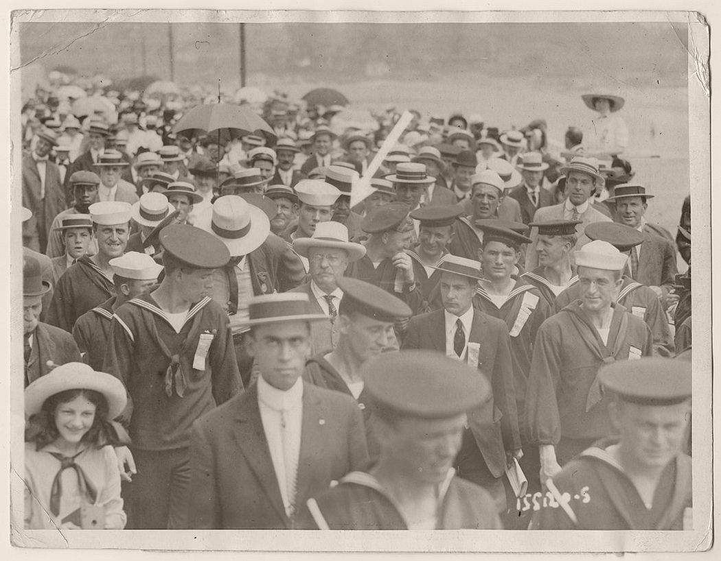 Theodore Roosevelt inside a crowd of sailors and other individuals on the boardwalk in Newport, Rhode Island. July 22, 1908.