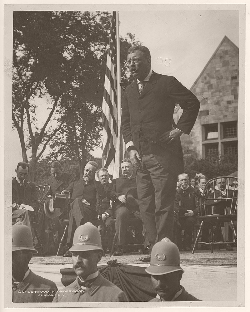 On August 25, 1902, President Theodore Roosevelt delivered a speech in Nahant, Massachusetts. Henry C. Lodge, governor of Massachusetts, is seated behind President Roosevelt, with his hand touching his head.
