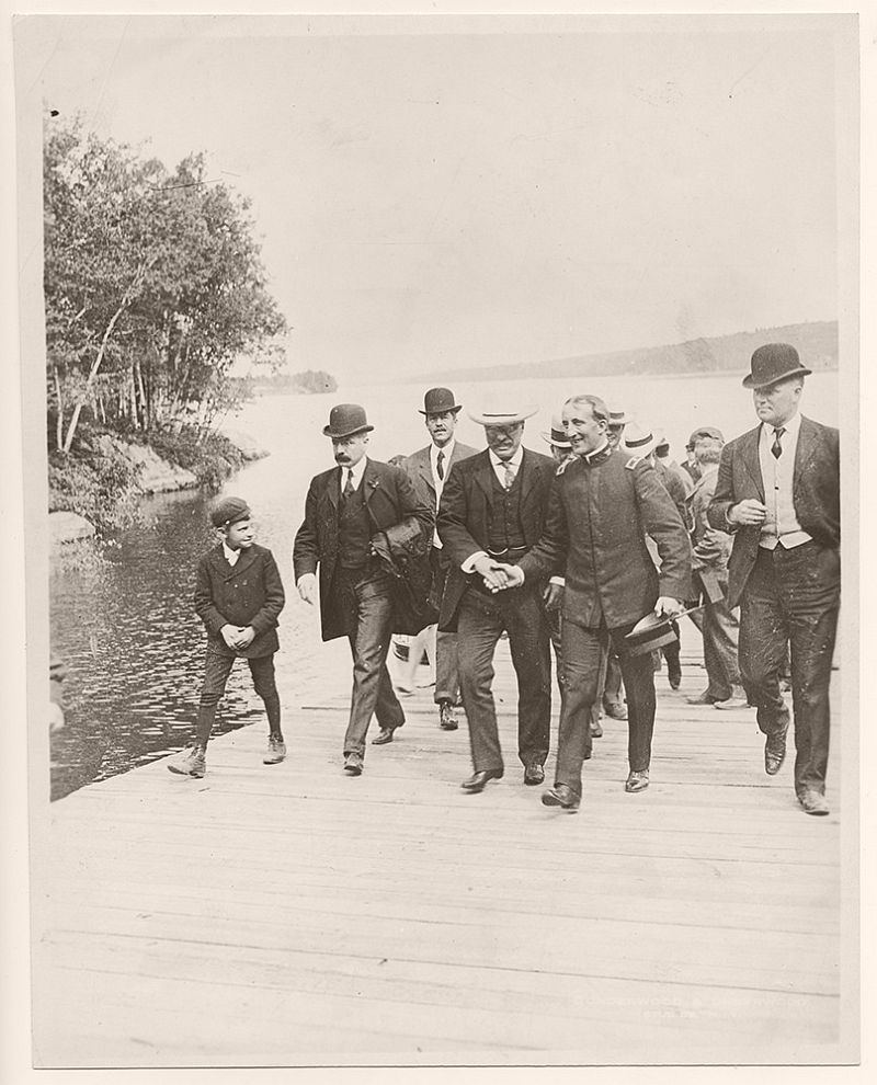 Theodore Roosevelt, during his New England tour, at Lake Sunapee in New Hampshire. In the photograph are George B. Cortelyou, Roosevelt's future secretary of Commerce and Labor, on Roosevelt's right, and William Craig, the first Secret Service agent ever killed in the line of duty, on the far right in the photograph. August 29, 1902.