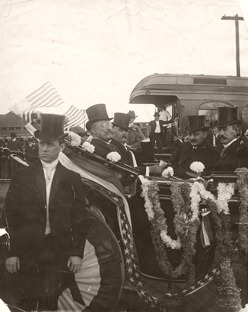 Taken on April 5th, 1905, this photograph is of Theodore Roosevelt and his party, during a brief stop in Sherman, Texas, while traveling to San Antonio to attend a reunion of the Rough Riders. Speaking for 15 minutes before a crowd of 35,000, he praised Texas as 'one of two or three greatest states in the Union', emphasized his own heritage from the south and the north and his delight in national reunification. Pictured in the foreground of the photograph, from left to right, are an unidentified man, Theodore Roosevelt, President of the United States, an unidentified man, William Loeb, Jr., Secretary to the President, and Cecil A. Lyon, Republican National Committeeman.