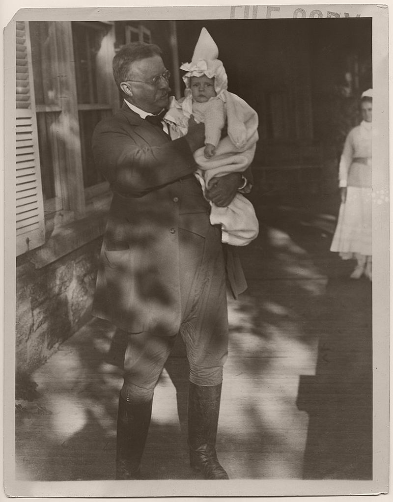 President Roosevelt holds one of his grandchildren on his porch. Oyster Bay, Nassau County, New York, ca. 1911-1919.