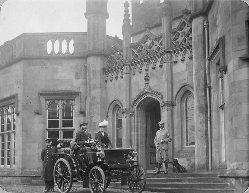 Inchrye Abbey entrance with couple in automobile, c. 1900.