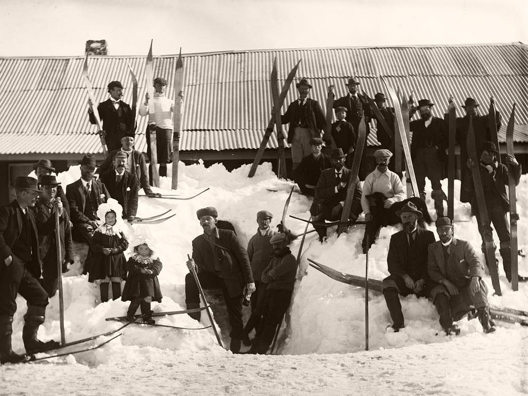 Several skiers from the 1900 Kiandra Snow Shoe Carnival posing in front of a building in the snow.