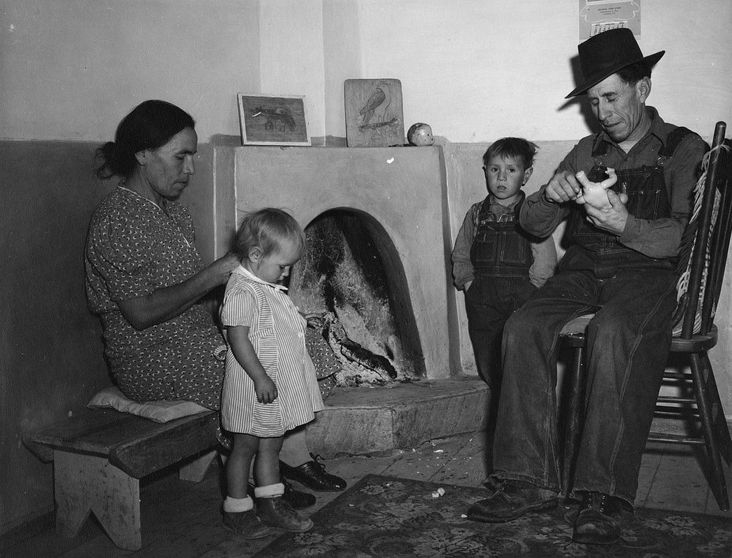 A family around the kiva fireplace, Trampas, New Mexico, 1943