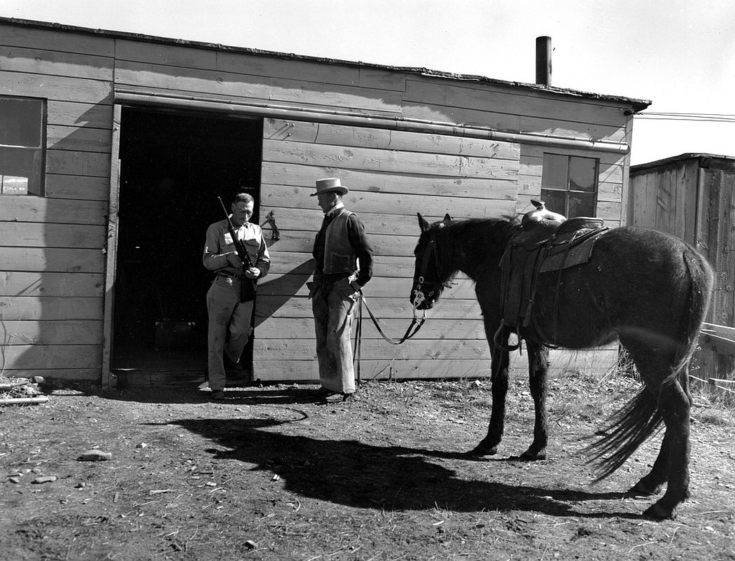 A gunsmith as well as a cattleman chatting in front of his shop, Moreno Valley, Colfax County, New Mexico, 1943