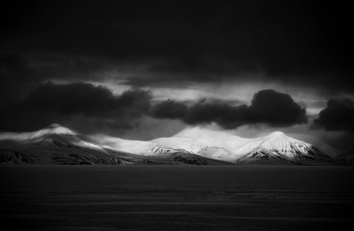 Black clouds on top of the snowy moutain © Laurent Baheux