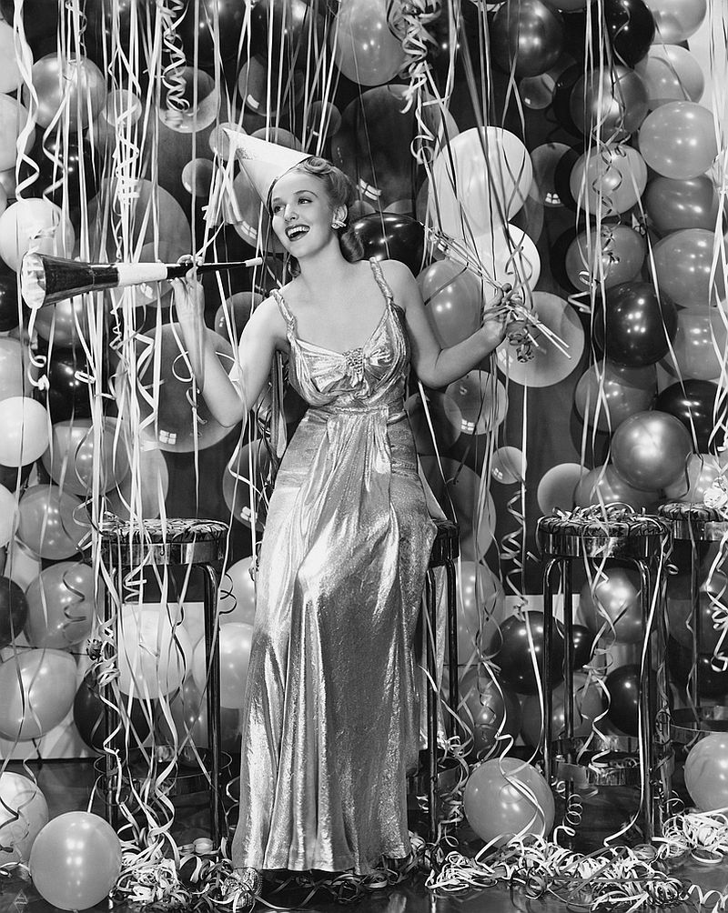 Woman celebrating with room full of balloons.